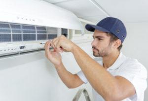 Homme installant une climatisation